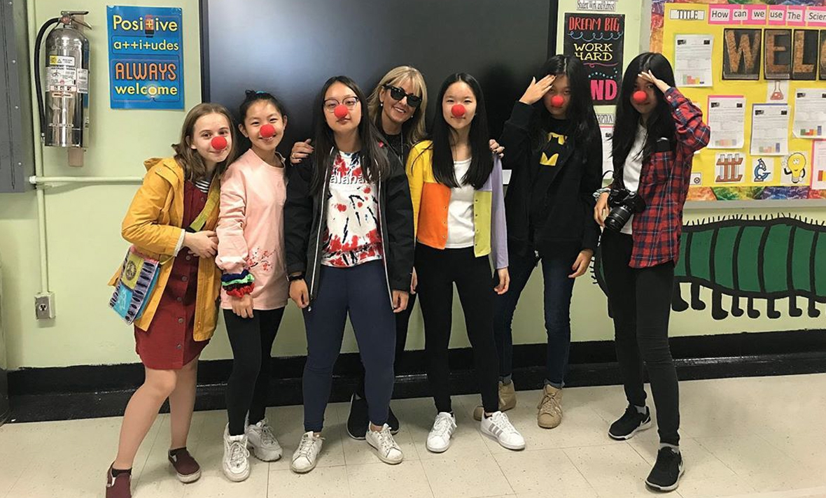 Class 8AE poses with Mrs. Eskenazi with red noses for Halloween