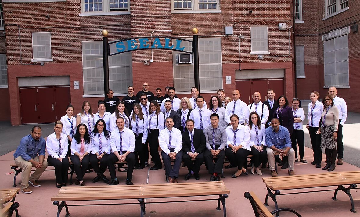 Group of SEEALL Academy teachers posing in school yard, wearing ties