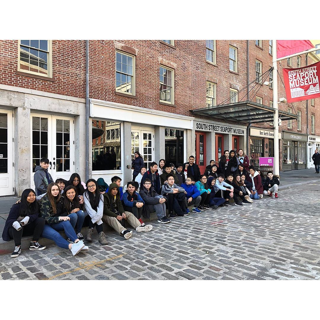 8th grade on a class trip, posing outside South Street Seaport Museum