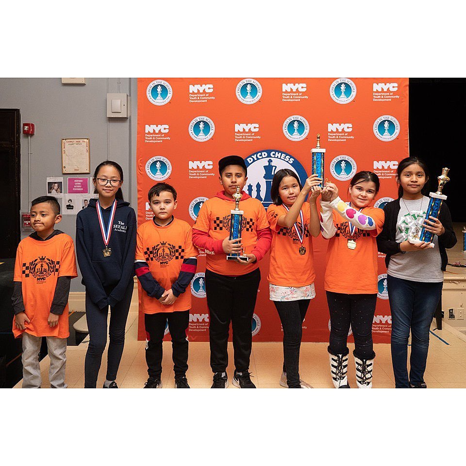 Chess students posing with their trophies